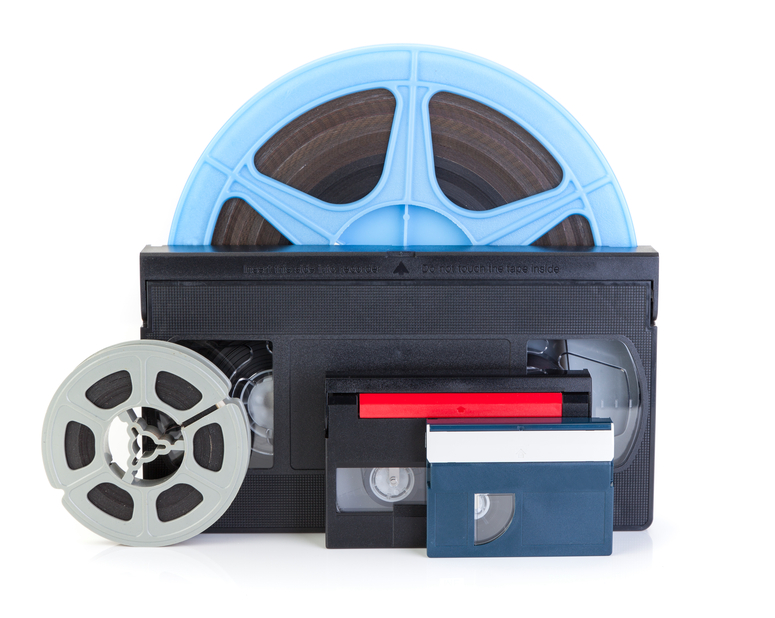 Video cassettes and film reels on white background with DVD, Concept for DVD transfer